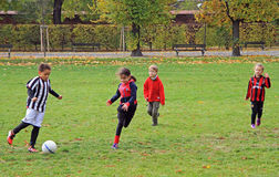 孩子在城市公园踢橄榄球 库存图片