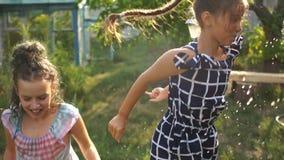 孩子在夏天雨中使用 儿童使用室外在下雨天 在重的阵雨下的女孩捉住的雨下落 影视素材