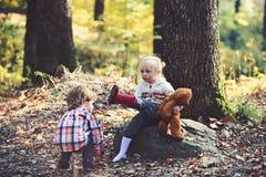 孩子在女孩脚上把红色起动放 准备好的孩子步行在秋天森林里 免版税库存照片