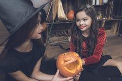 孩子在妖怪服装打扮了万圣夜通行证的一盏被雕刻的南瓜灯 免版税库存照片