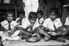 孩子在学校吃他们的膳食 免版税库存照片