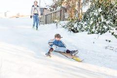 孩子在守旧派样式的雪滑与硬木 库存图片