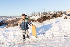 孩子在守旧派样式的雪滑与硬木 免版税图库摄影