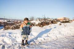 孩子在守旧派样式的雪滑与硬木 库存照片