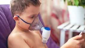 孩子在家做吸入雾化器 在面孔佩带吸入蒸气的面具雾化器喷洒了疗程入肺  库存照片