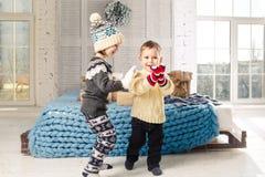孩子在家站立和使用在卧室的兄弟和姐妹在与箱子,在圣诞节背景的礼物的床附近  库存照片