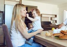 孩子在屋子里喂养她的母亲 库存图片