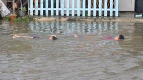 孩子在巴吞他尼府一条被充斥的街道游泳在2011年10月 免版税库存照片