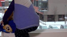 孩子在幅射器上把玩具熊有围巾的玩具朋友放在窗口附近 雪秋天 股票视频