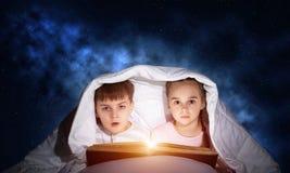 孩子在床上的读可怕故事 免版税库存照片