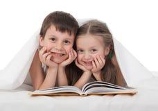 孩子在床上读了一本书 免版税库存图片