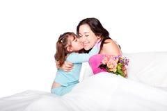孩子在床上给花和亲吻妈妈 免版税库存照片
