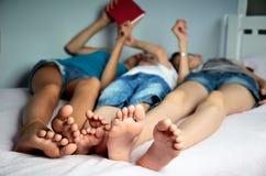 孩子在床和戏剧上说谎在片剂 他们的腿 免版税图库摄影