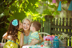 孩子在庭院里亲吻他的母亲 库存照片