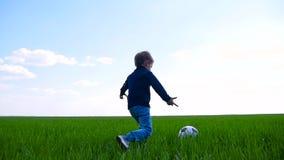 孩子在慢动作的一个绿草领域踢足球并且跑 股票视频