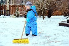 孩子在房子附近清除雪 免版税库存图片