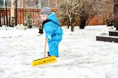 孩子在房子附近清除雪 库存图片