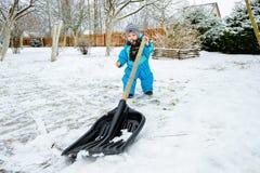 孩子在房子附近清除雪 免版税库存照片