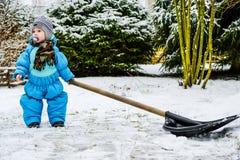 孩子在房子附近清除雪 库存照片