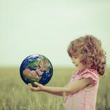 孩子在手上的拿着地球 图库摄影