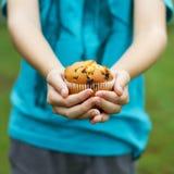 孩子在手上的拿着松饼 库存图片