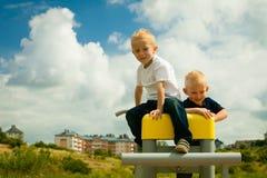 孩子在操场哄骗使用在休闲设备的男孩 免版税库存照片