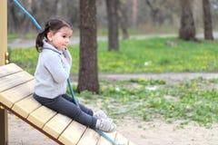 孩子在操场攀登一条绳索 免版税图库摄影