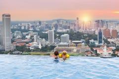 孩子在新加坡屋顶上面游泳池游泳 免版税图库摄影