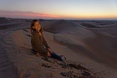 孩子在日落的沙漠 免版税库存图片