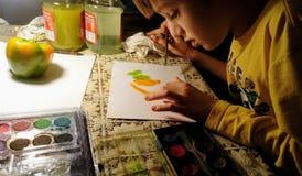 孩子在晚上画与油漆的绿色和黄色喇叭花胡椒 免版税库存图片