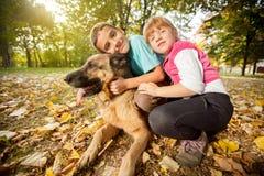 孩子在有一只德国牧羊犬的公园 免版税图库摄影