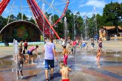 孩子在有喷泉的操场洗涤在热的夏天 免版税库存图片