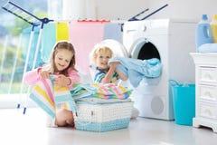 孩子在有洗衣机的洗衣房 免版税库存图片