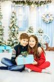 孩子在有礼物的一间屋子里坐 男孩和g 图库摄影