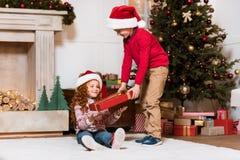 孩子在有礼物的圣诞老人帽子 库存照片