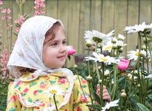 孩子在有花的庭院里 免版税库存图片