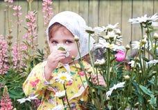 孩子在有花的庭院里 免版税库存照片