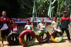孩子在村庄演奏在河的快乐的水滑道, 免版税库存图片