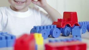 孩子在桌上使用与玩具汽车和色的块 股票录像