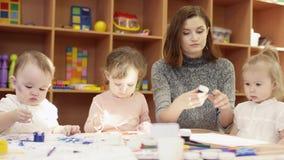 孩子在桌和油漆上坐画纸,幼稚园老师打开一个罐头油漆并且给它a 股票录像