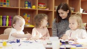 孩子在桌和油漆坐画纸,坐在他们旁边的幼稚园老师上并且服务罐头  股票录像