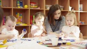 孩子在桌和油漆坐画纸,坐在他们旁边的幼稚园老师上并且画某事 股票视频