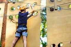 孩子在森林冒险公园 在橙色盔甲的孩子和在高绳索足迹的蓝色T恤杉攀登 敏捷性技能和上升 库存图片