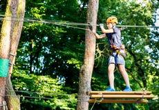 孩子在森林冒险公园 在橙色盔甲的孩子和在高绳索足迹的蓝色T恤杉攀登 敏捷性技能和上升 免版税库存照片