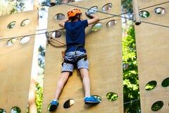 孩子在森林冒险公园 在橙色盔甲的孩子和在高绳索足迹的蓝色T恤杉攀登 敏捷性技能和上升 免版税库存图片