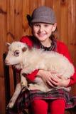 孩子在椅子和坐她的膝部喜爱羊羔 在农场 库存照片