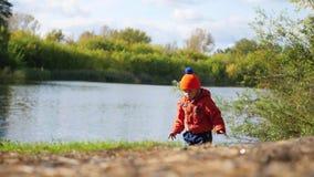 孩子在池塘和投掷的石头的银行站立 在新鲜空气的步行 股票录像