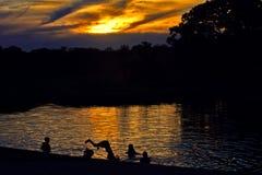 孩子在湖潜水在黄昏 免版税库存照片