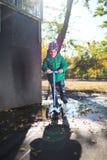 孩子在滑行车的水坑滚动 库存照片