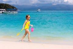孩子在热带海滩使用 沙子和水玩具 免版税库存图片